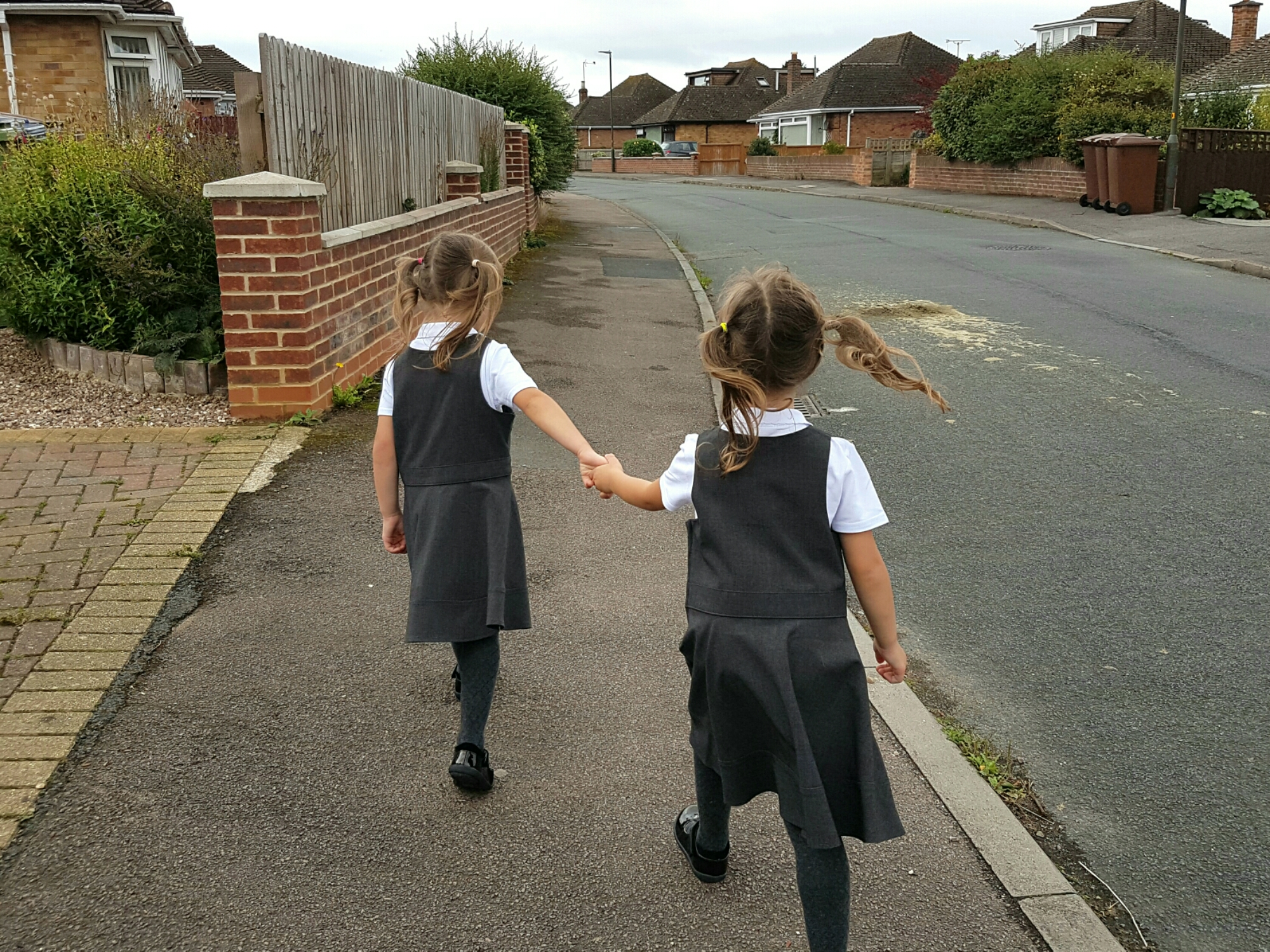 The twins start school. Image of my twins walking to school holding hands.