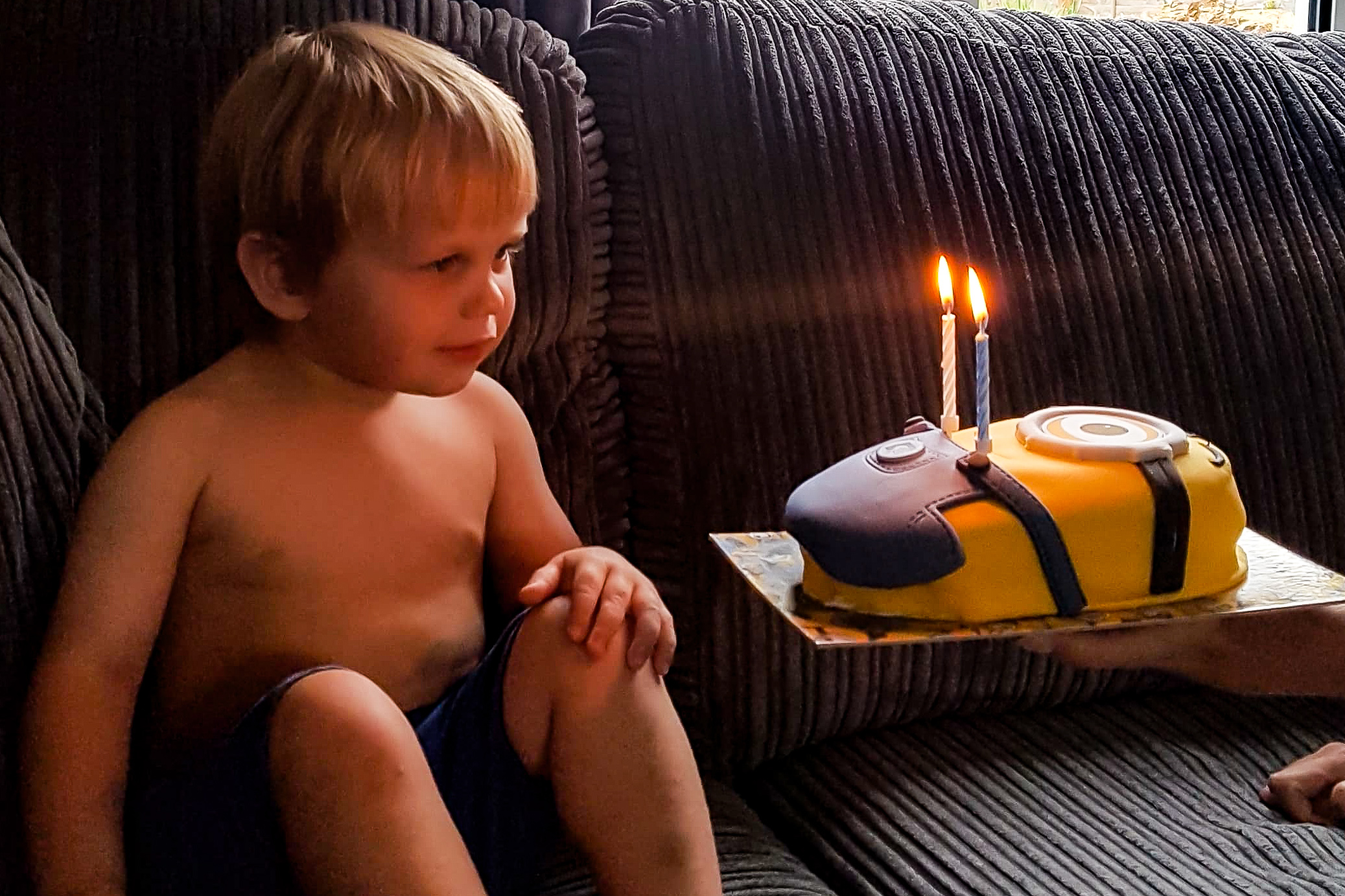 toddler blowing out candles, 2nd birthday, birthday cake, minions cake,