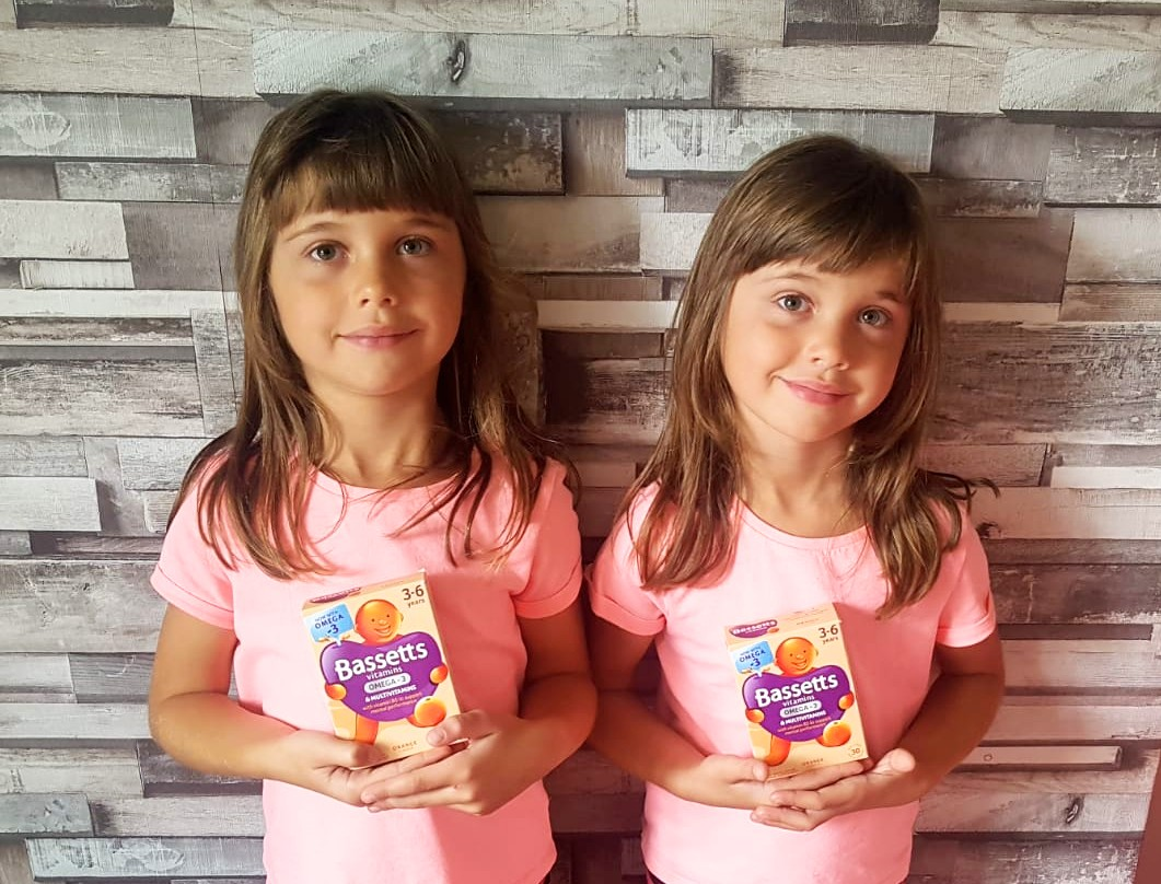 6 year old twins holding Bassetts Omega-3 + Multivitamins for 3-6 year olds