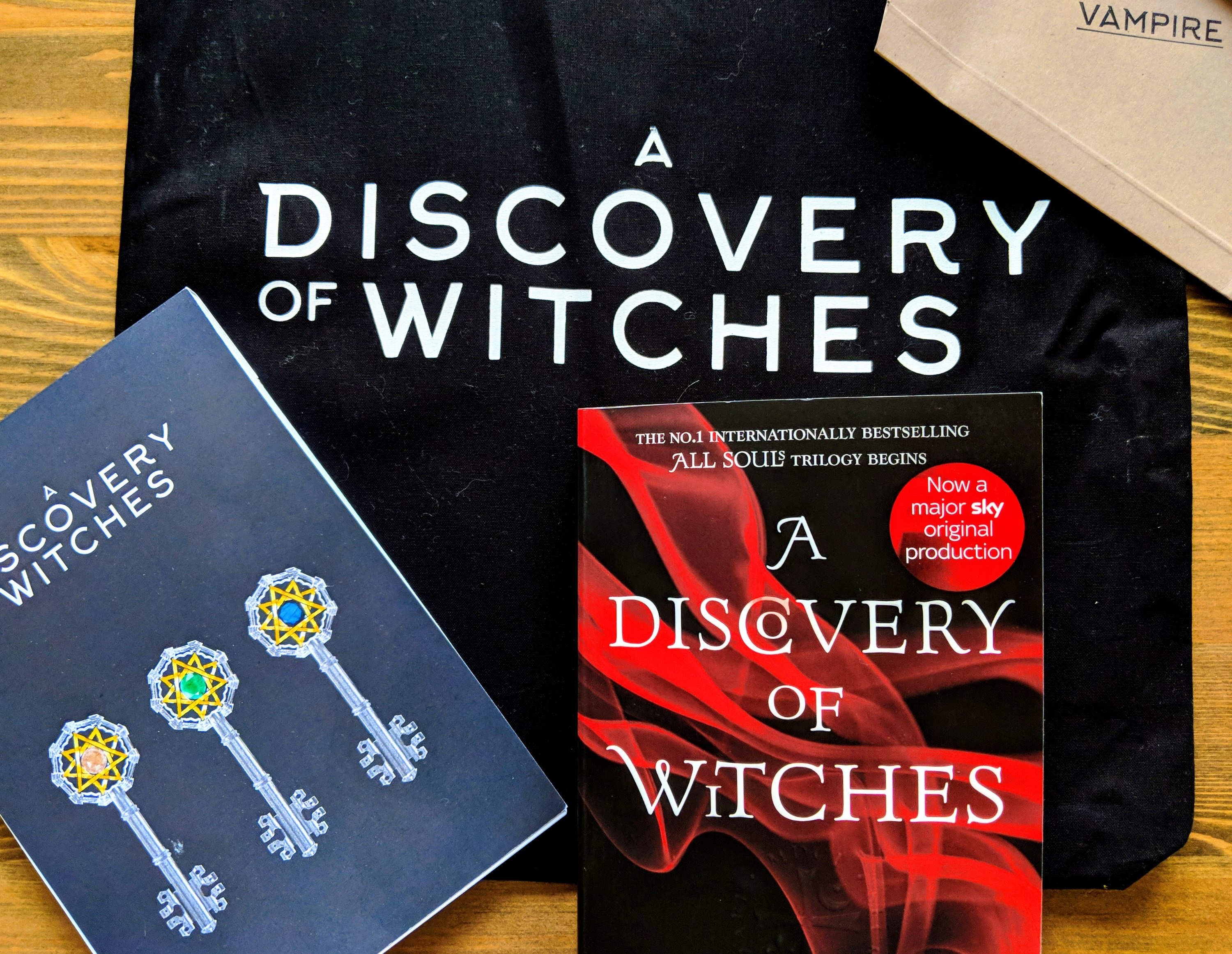 A Discovery of Witches book by Deborah Harkness with a notepad and tote bag from the launch of A Discovery of Witches TV Series