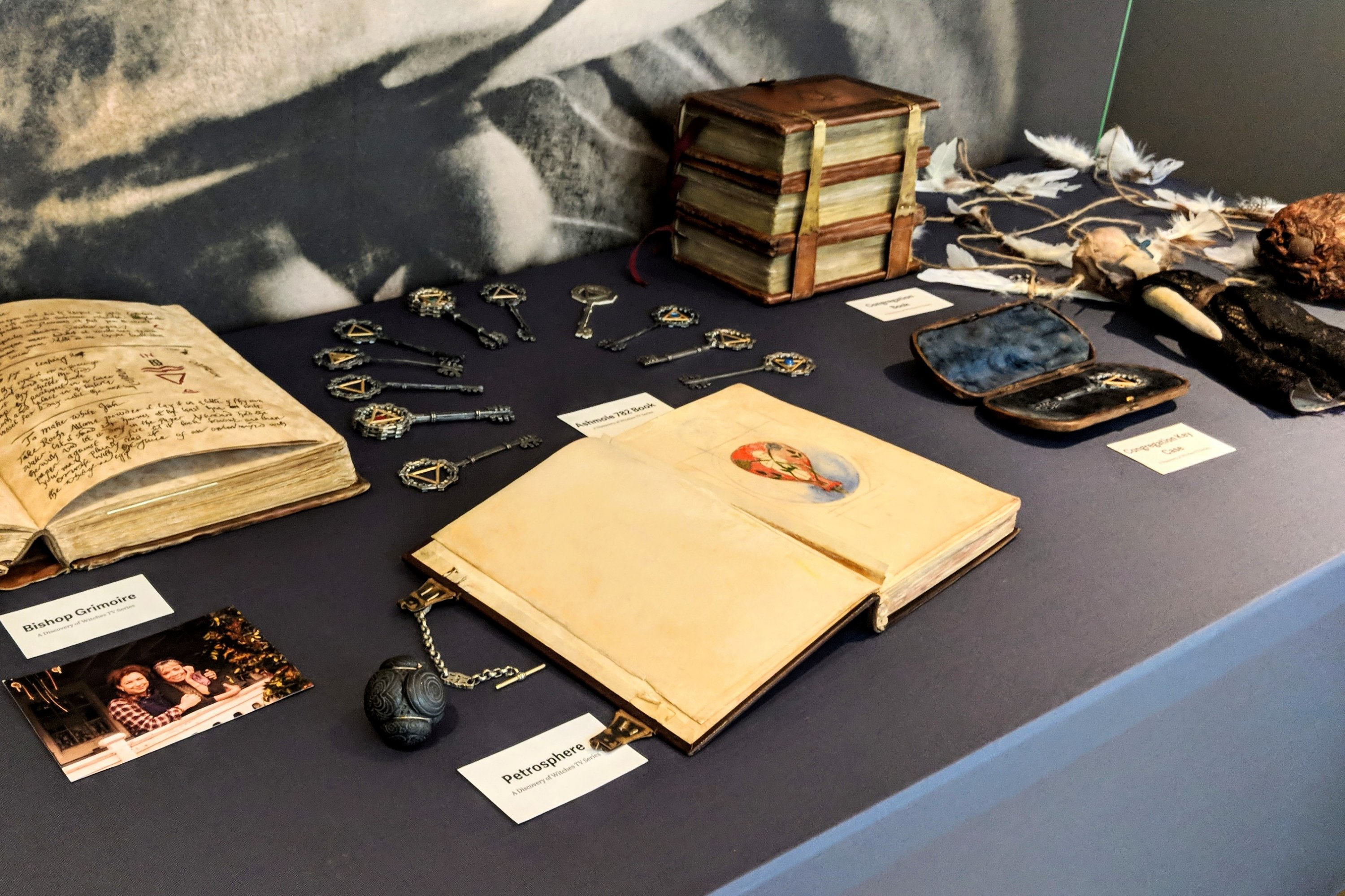 Props from the set of A Discovery of Witches TV series, including Ashmole 782 book, keys bearing alchemy symbols, books, a voodoo doll and other magical objects from the TV show and book by Deborah Harkness.