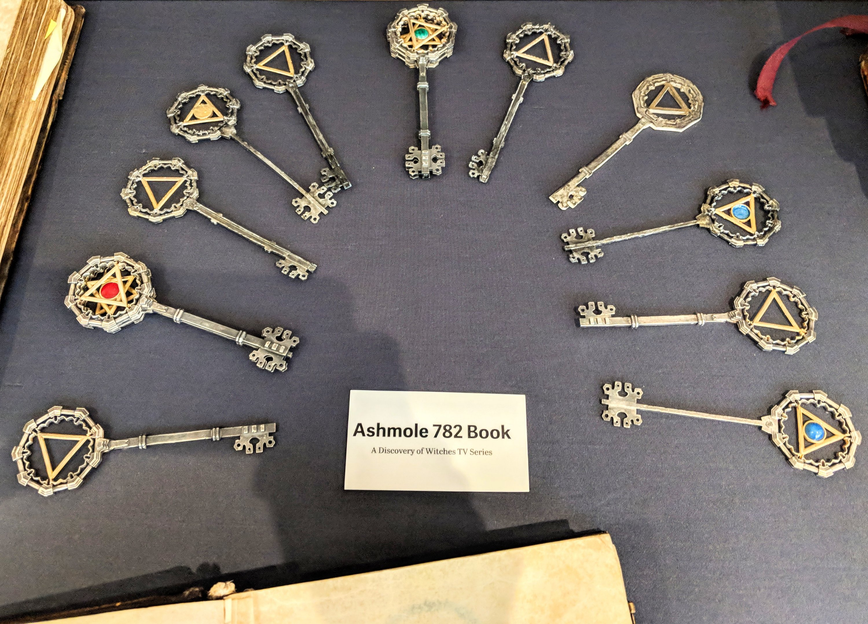 Props from the set of A Discovery of Witches TV series, including a collection of keys bearing alchemy symbols.