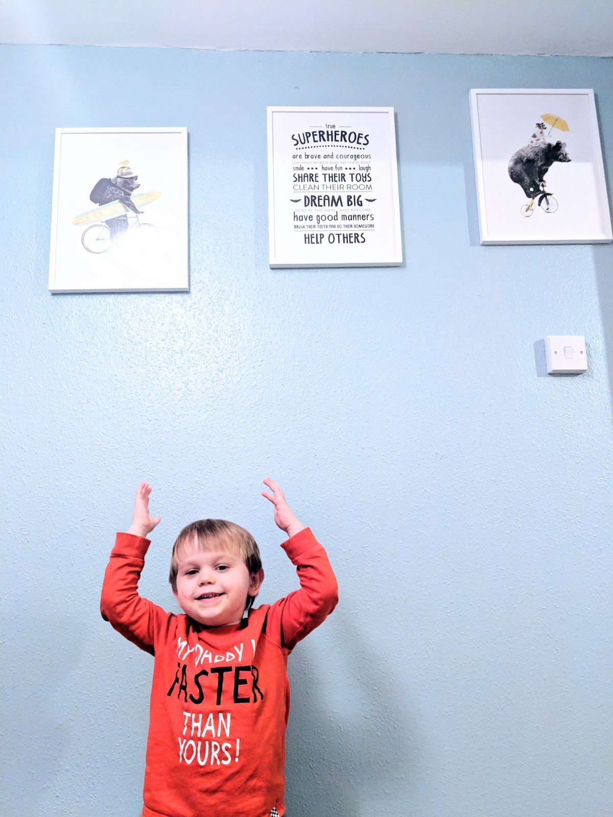 toddler showing off the Desenio art on his walls