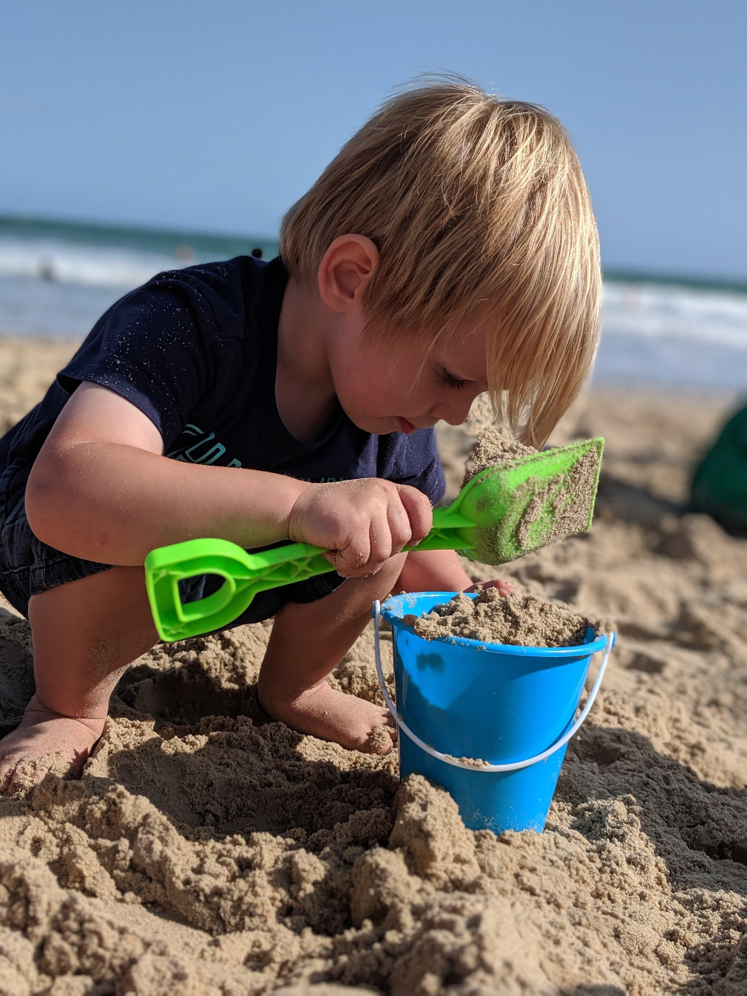 toddler on the beach making sandcastles