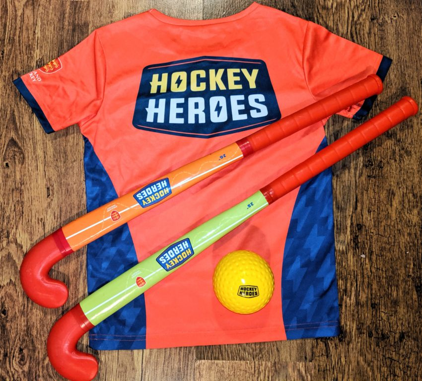 Orange Hockey Heroes tshirt with two hockey sticks and a lightweight hockey ball. These are the kit that children get when they join the Hockey Heroes programme with England Hockey.