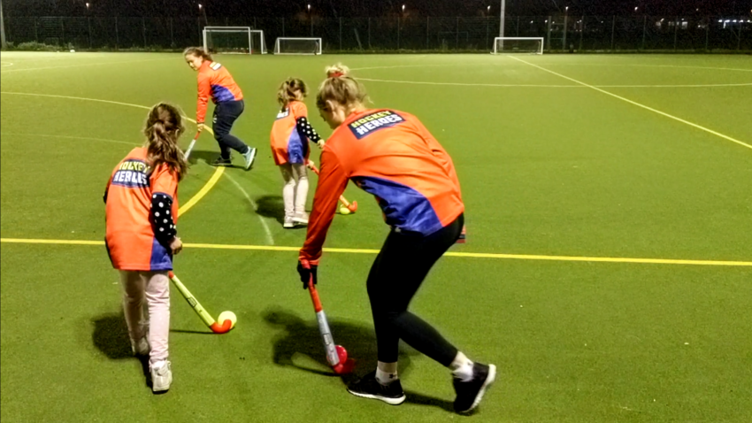 Two children playing hockey with their two hockey coaches as part of the Hockey Heroes initiative by Hockey England