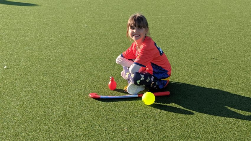 7 year old sitting on astro turf with her hockey stick and hockey ball waiting to play hockey with England Hockey's Hockey Heroes programme