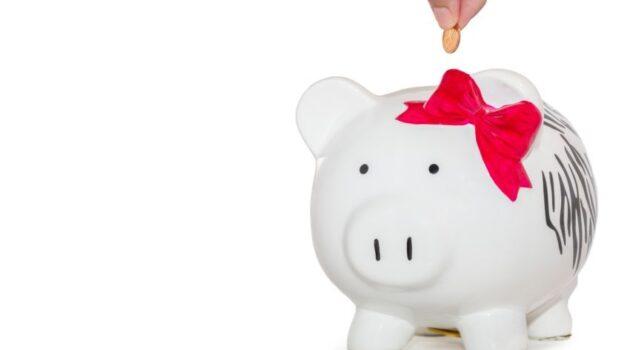 putting a coin into a white ceramic piggy bank