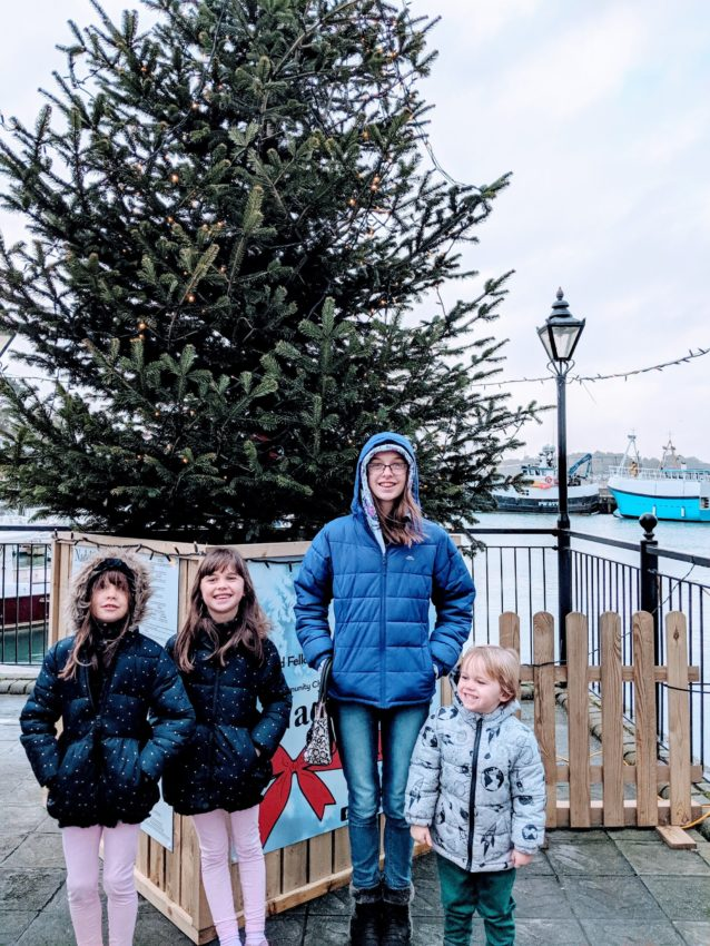 Four children standing in front of an outdoor Christmas tree in Padstow, Cornwall