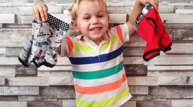To illustrate an article about toddler toilet training, this photo depicts a 3 year old boy proudly holding up two new pairs of pants.