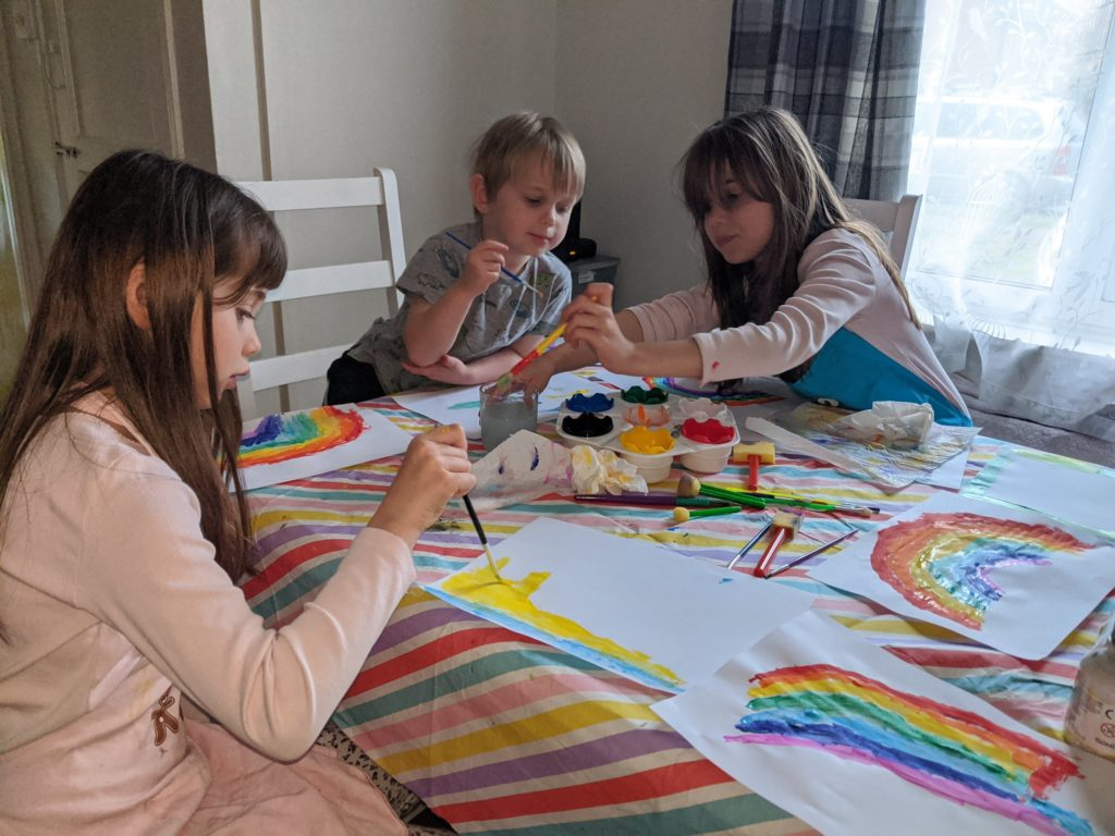 Children painting rainbows for the rainbow trail, during the coronavirus lockdown in the UK