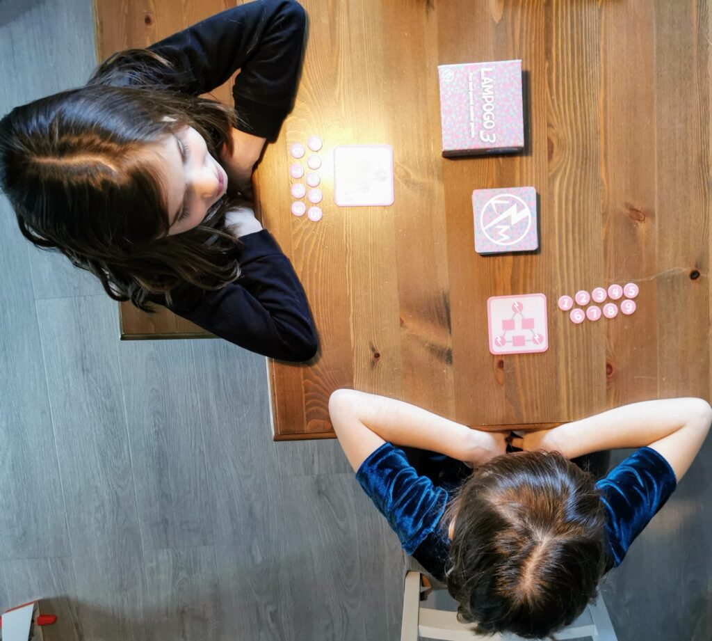 birds eye view of 8 year old twins playing Lampogo 3 at a table